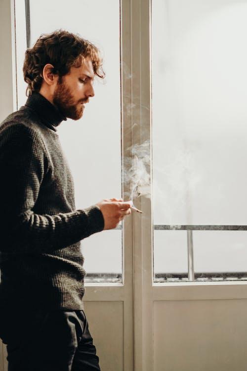흡연하는 동안 흰색 나무 프레임 된 유리 창 옆에 서있는 검은 스웨터를 입고 남자