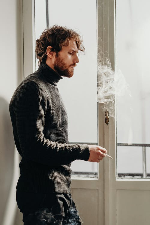 Side View Photo of Man in Black Sweater Standing Beside White Wooden Door Smoking