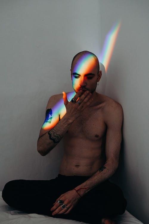 Photo of Man Sitting Near White Wall