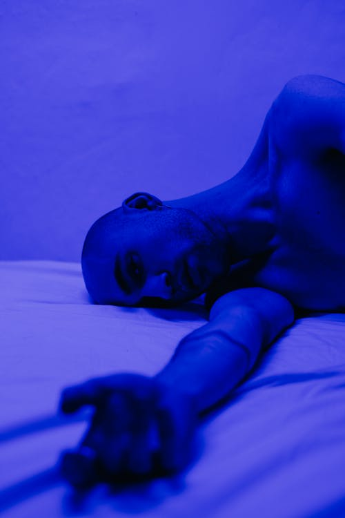 Photo of Man Lying on Bed