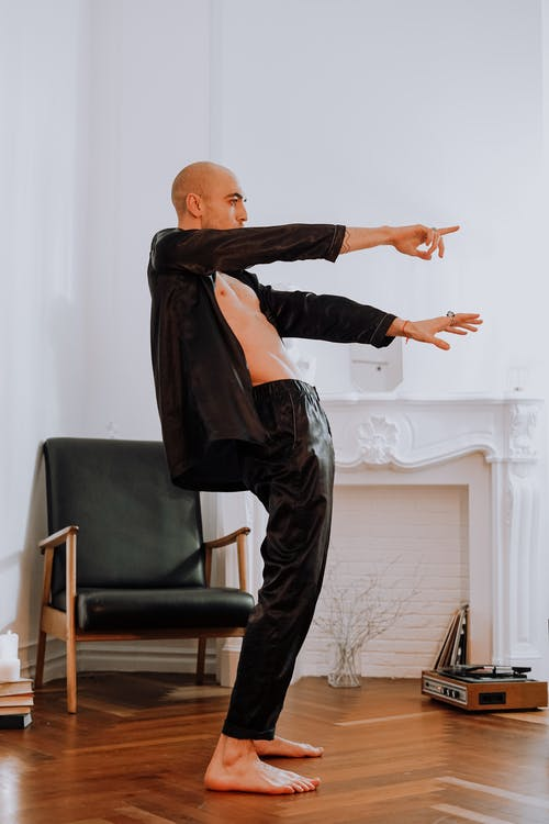 Man in Black Jacket and Black Pants Standing on Wooden Flooring