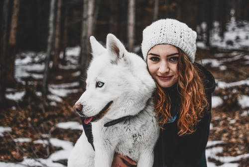 Woman Wearing White Knit Cap While Hugging Her White Siberian Husky