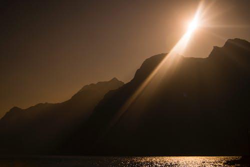 Gratis lagerfoto af bjerge, sol, sollys, solstråle