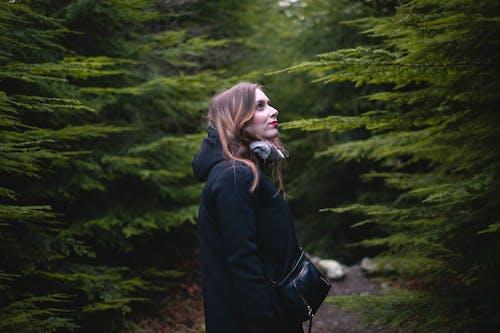 Woman Standing Between Trees