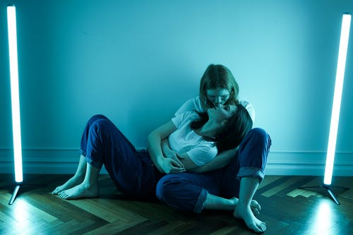 Women in Blue T-shirt and Blue Denim Jeans Sitting on Floor
