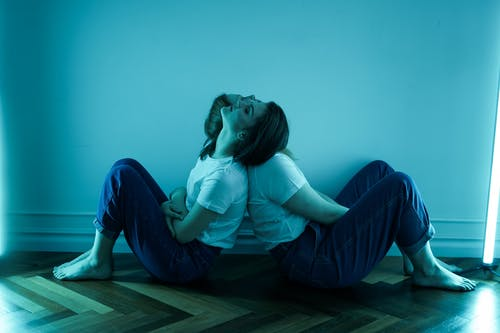 Women in White T-Shirt and Blue Denim Jeans Sitting on Floor