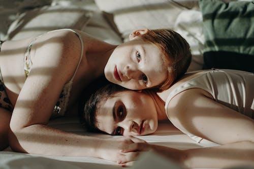 Women Lying on White Bed