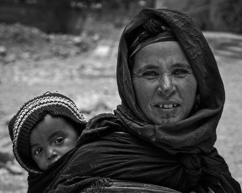 Grayscale Photo of Woman in Black Hijab Carrying Baby Wearing a Knit Cap