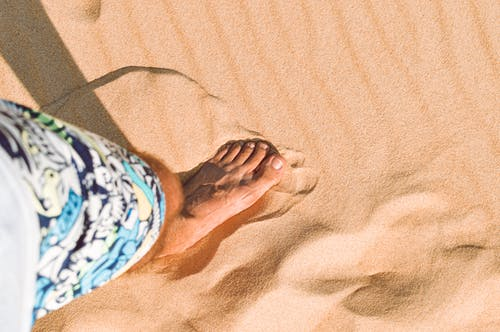 Person in Blue and White Floral Shorts Standing on Brown Sand