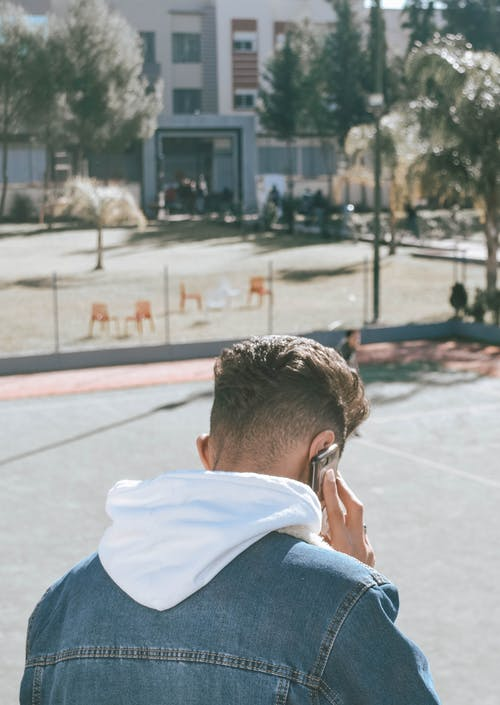 Back view of modern youngster in denim jacket having phone call on sports ground in city