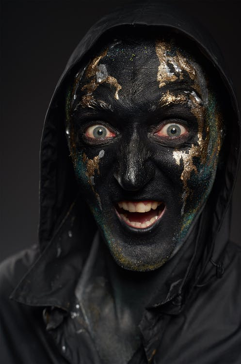 Person in Black and Golden Face Mask