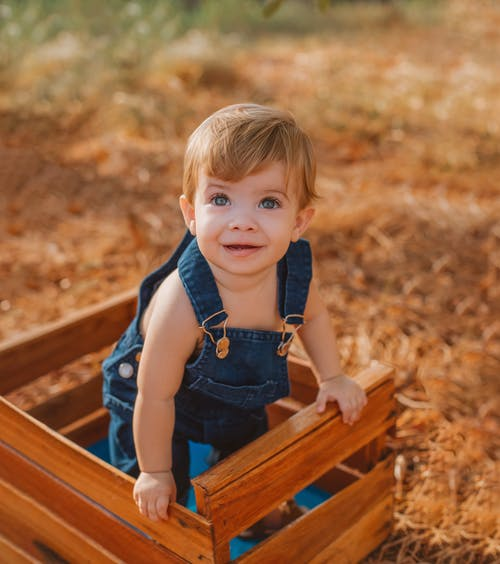 Baby in a blue dangerie Standing in a Brown Wooden Bench