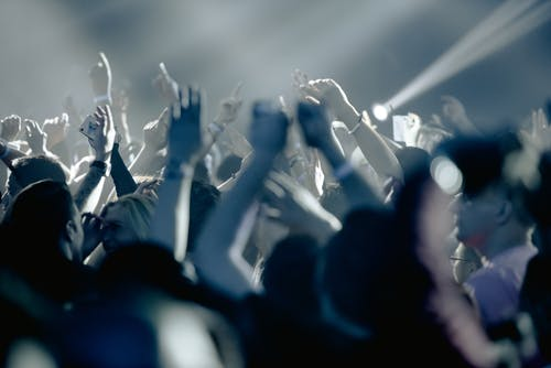 Thrilled people raising hands in excitement and cheering during live concert in dark club