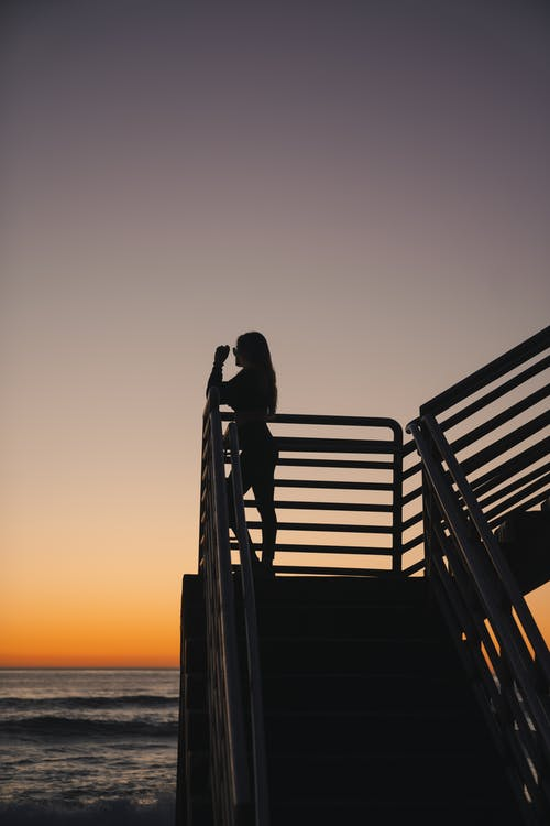 Silhouette Of  A Woman Standing on Wooden Dock during Sunset