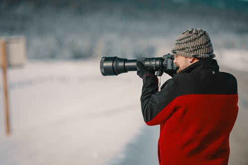 Man in Red and Black Sweater Using Black Dslr Camera
