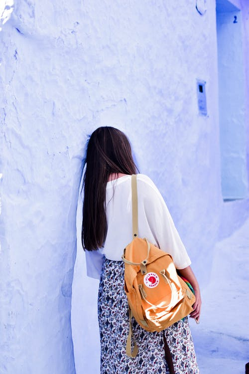 Woman in White Shirt Leaning on Blue Concrete Wall
