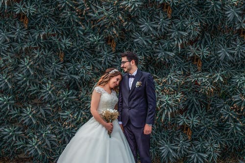 Woman in White Wedding Dress Holding Bouquet of Flowers Leaning on Man in Black Suit