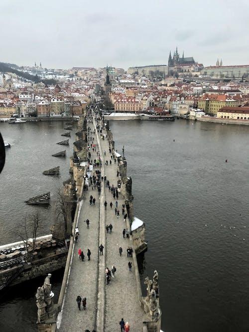 Aerial Shot of People Crossing on Concrete Bridge