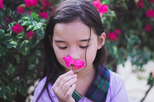 Girl in Purple Top Holding While Smelling Pink Flower