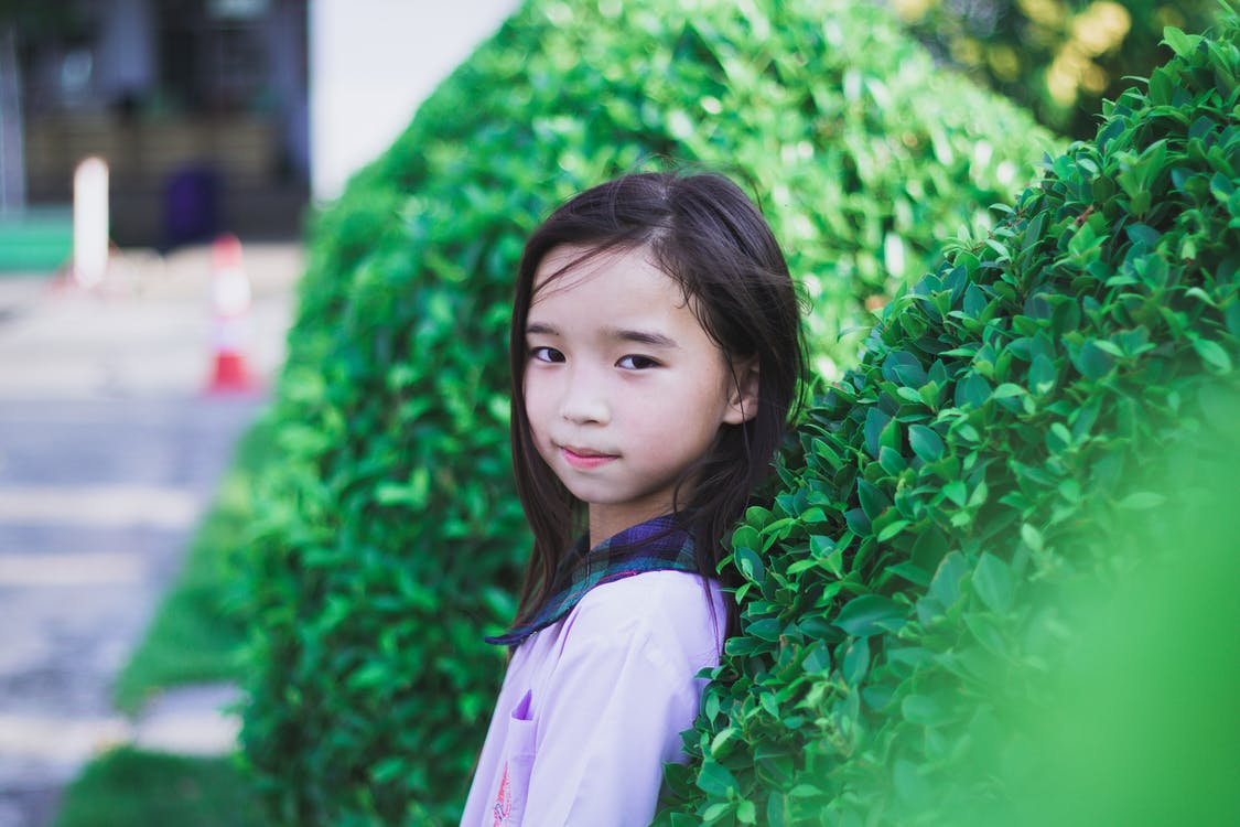 Girl in Purple Long Sleeve Shirt with Green and Black Plaid Collar Standing Beside Green Plant