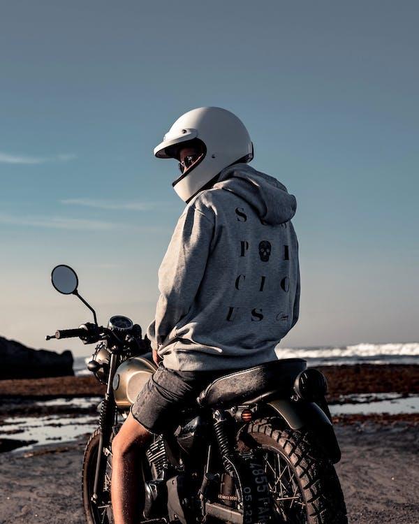 戴著白頭盔騎摩托車的人