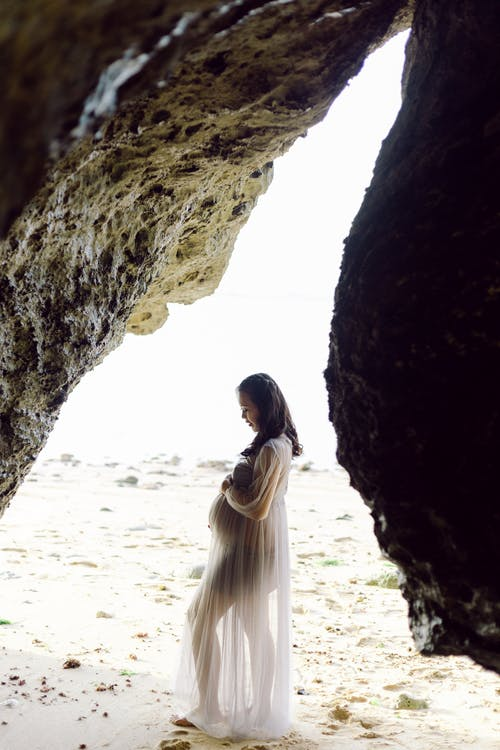 Pregnant Woman Standing on White Sand