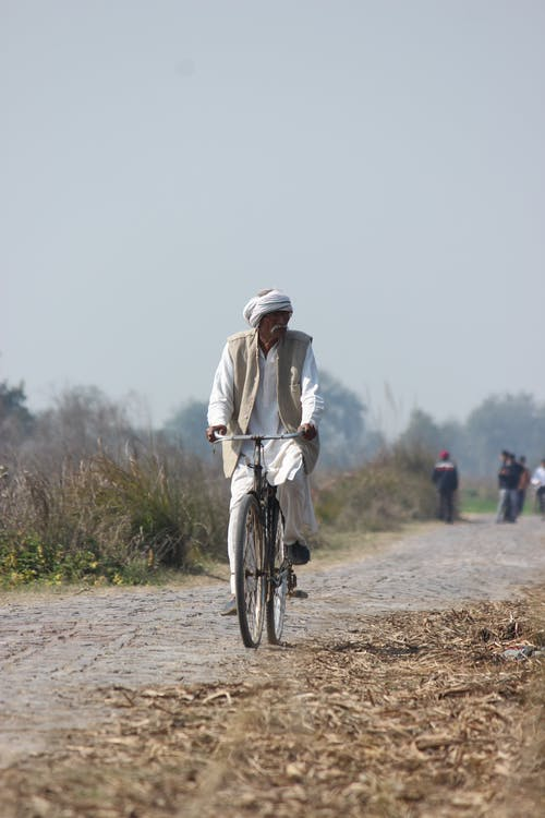 Man in White Long Sleeves Riding Bicycle