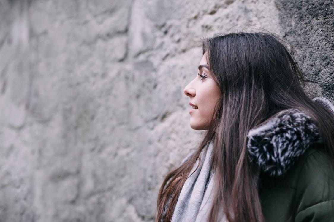 Woman Wearing Gray Winter Coat Leaning on Wall