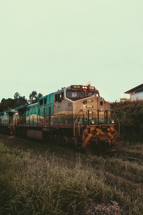 Green and Brown Train on Rail Tracks