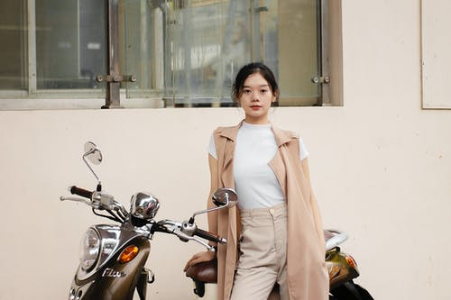 Stylish ethnic female teenager leaning on scooter on street