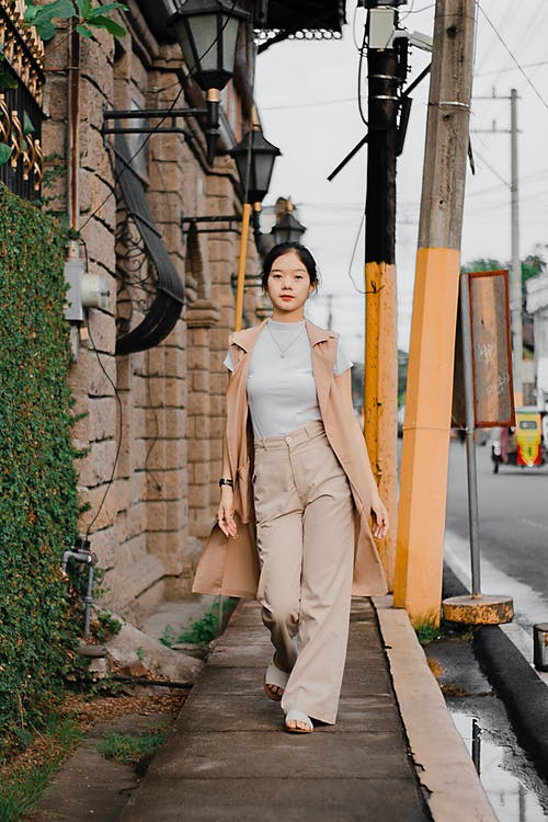 Stylish young ethnic woman walking on city street near aged building