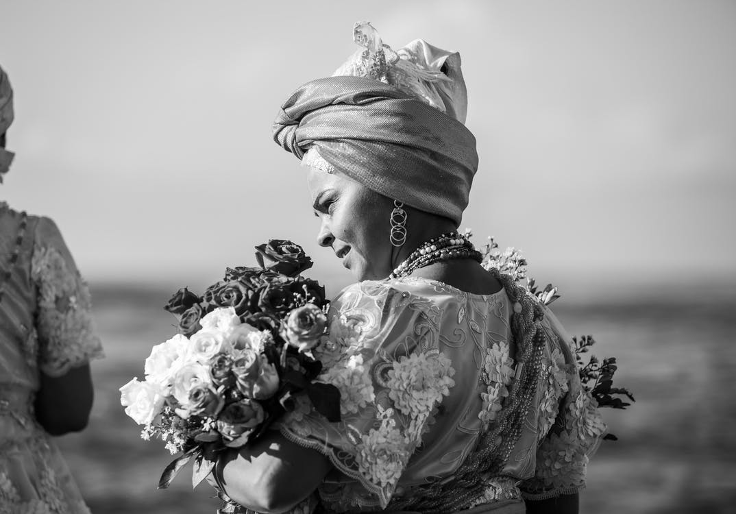 Gray Scale Photo of Woman Holding Flower Bouquet
