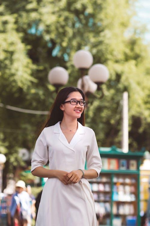 Woman in White Dress Wearing Black Framed Eyeglasses Smilling