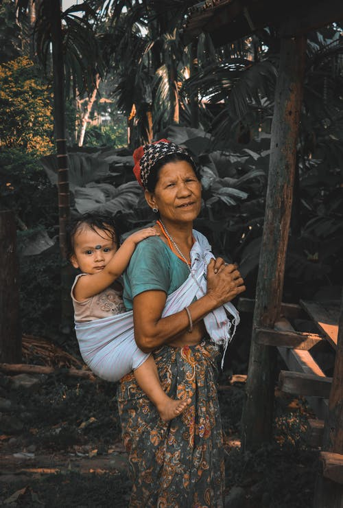 Woman Carrying Baby on Her Back