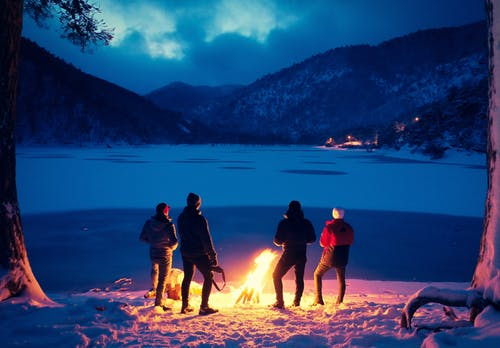 Group of tourists near bonfire in winter highlands