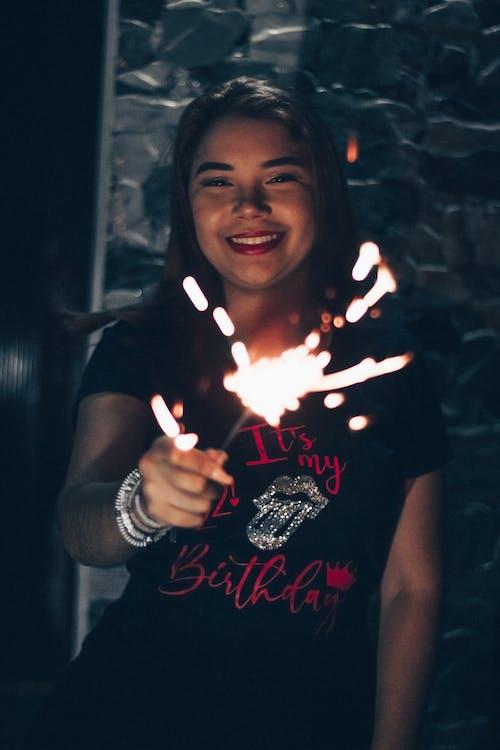 Mulher Sorridente Em Uma Camiseta Preta Com Gola Redonda Segurando Um Diamante Aceso