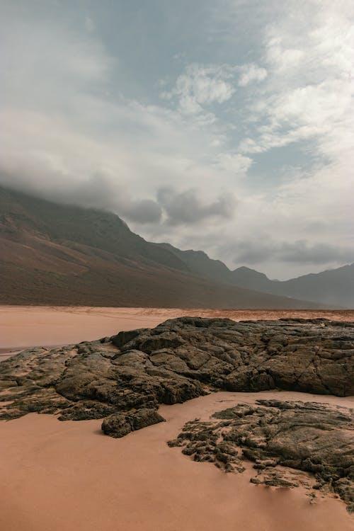 Brown Rocky Mountain Near Body of Water