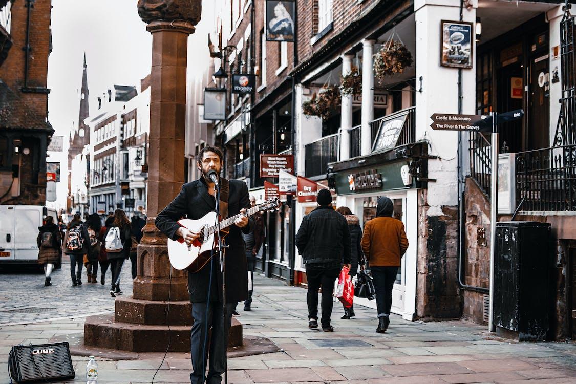Man Standing on Street Playing Guitar
