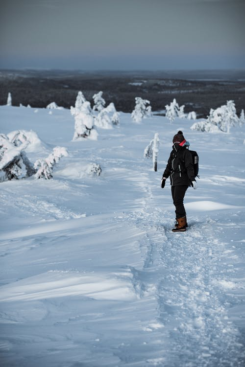 Person in Black Jacket and Black Pants Standing on Snow Covered Ground