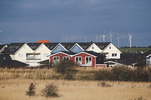 White and Red Houses on Brown Grass Field Under Gray Sky