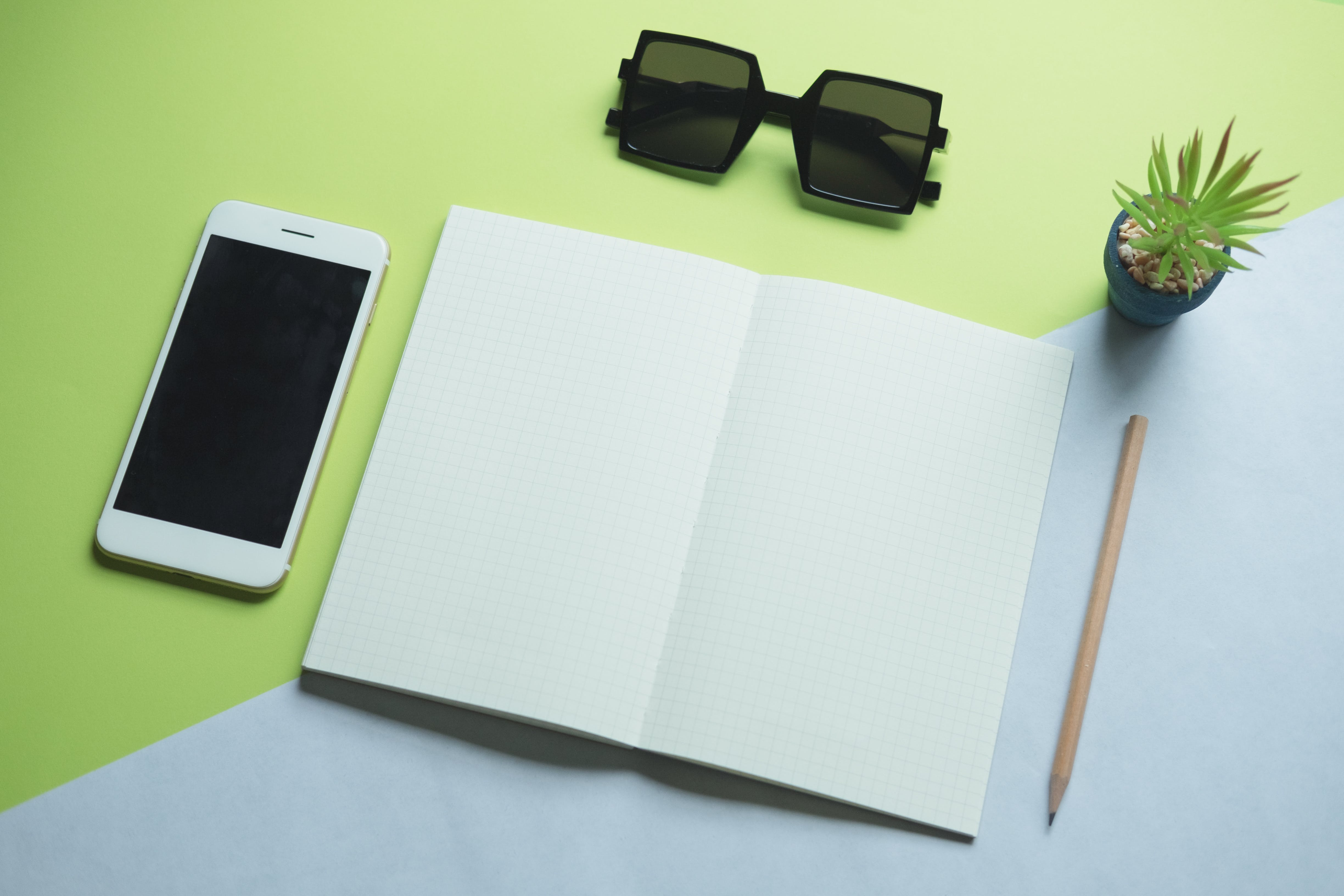 Free stock photo of sunglasses, smartphone, desk, notebook