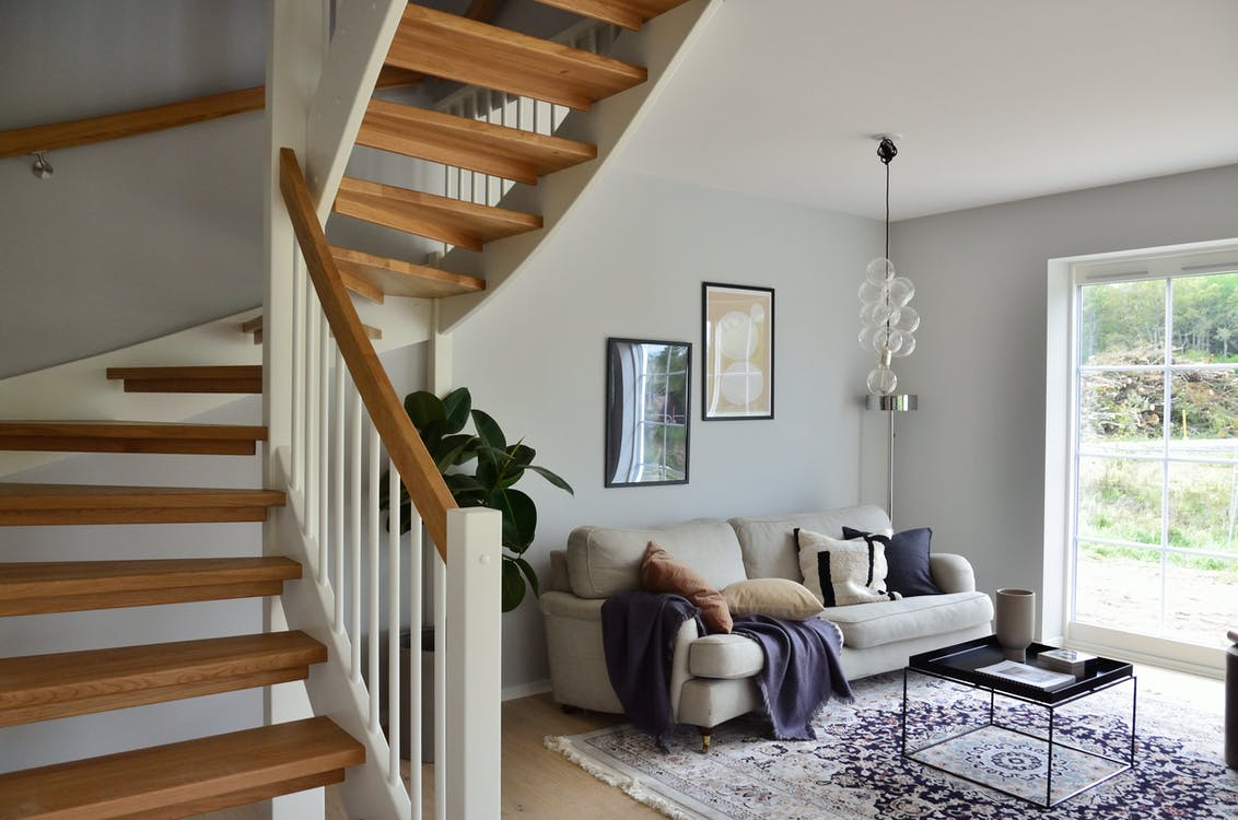 White Sofa Beside Brown Wooden Staircase