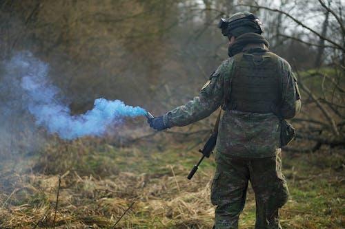 Mann In Der Militäruniform, Die Einen Signalrauch Hält