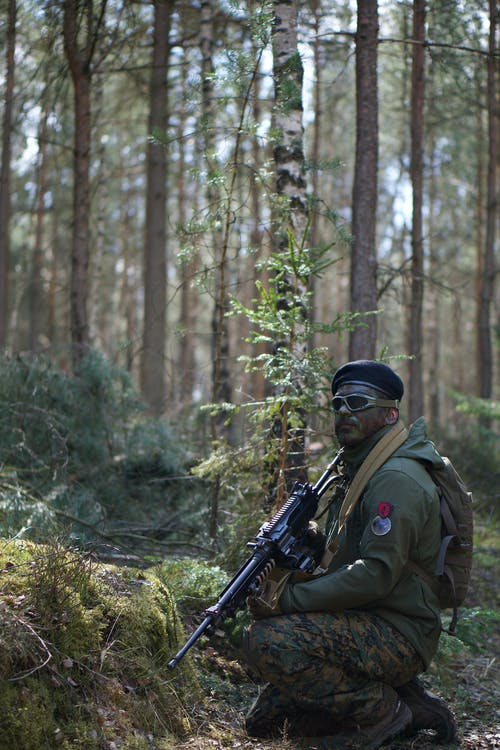 Man in Green Jacket Holding a Black Rifle in Forest