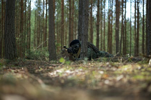 Man in Military Uniform  and a Backpack Lying on Ground Surrounded by Trees