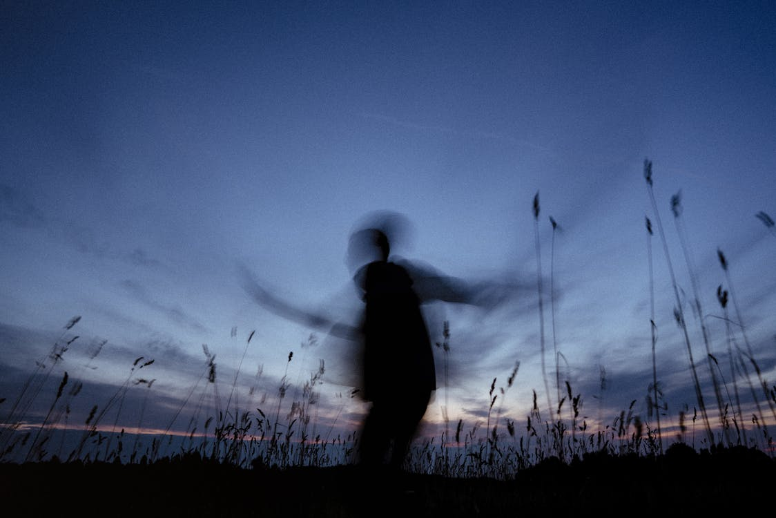 Silhouette of Man Standing on Grass Field during Night Time