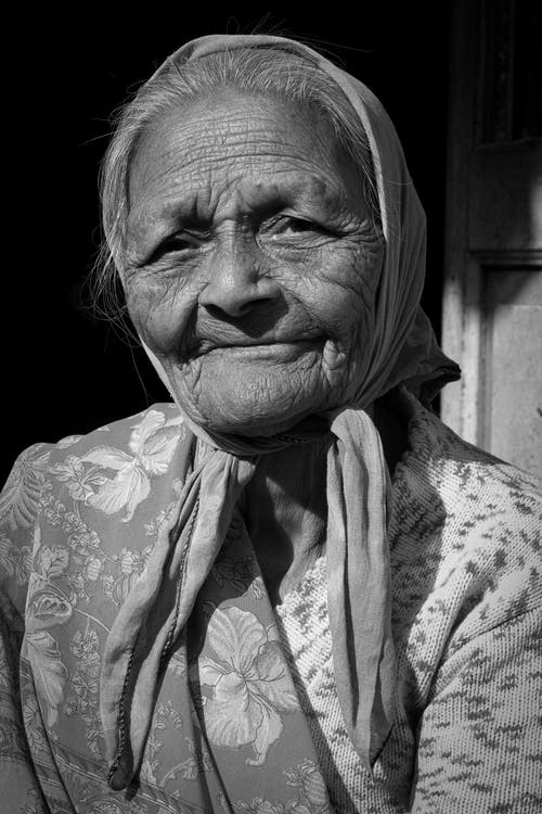 Grayscale Portrait Photo of an Elderly Woman Wearing Headscarf
