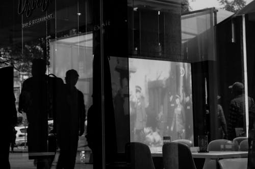 Silhouette Of People Standing Outside A Restaurant