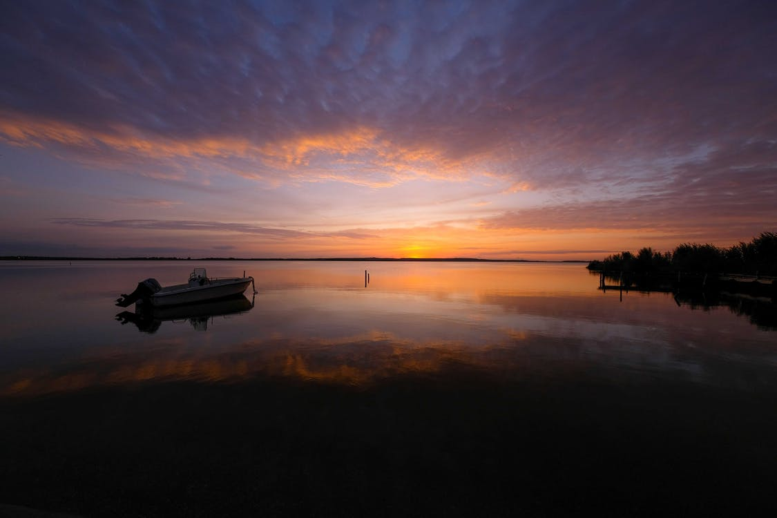 Silhouette of Boat on Calm Water during Sunset