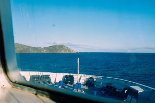 Through window of modern vessel floating on rippling sea against blue sky with rocky mountain in distance in coastal terrain